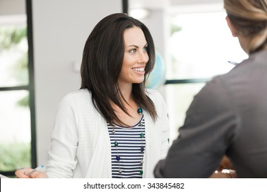Young colleagues sitting at desk and having discussion in bright office