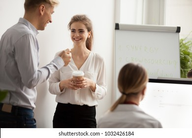 Young colleagues talking laughing at coffee break in corporate office, smiling man and woman having funny conversation standing in coworking, millennial employees flirting joking at work together