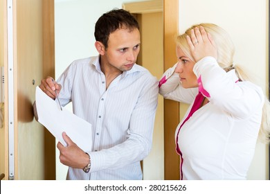 Young collector is trying to get the arrears from stressed woman at home door. Focus on the man