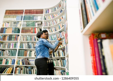 Young college Afro-American students taking book from shelf in library. Handsome young Afro-American man and woman in library.