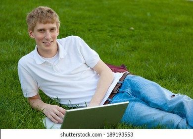 A young college age boy with a laptop computer sitting on grass outside
