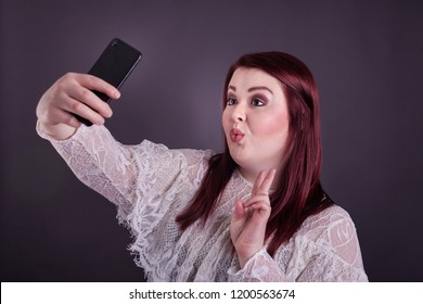 Young college aged woman holding cell phone taking a selfie puckered lips giving peace sign