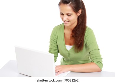 A young college girl sitting in front of a laptop, isolated on white