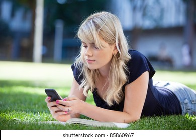 Young college girl using cell phone while lying on grass