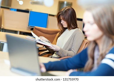young college student girl working in a library with books