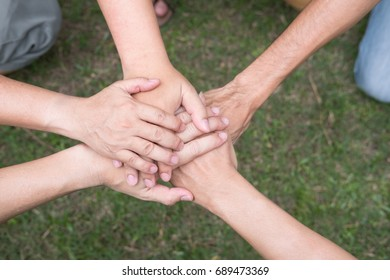 young college student joining united hand, start up business team touching hands together - unity, harmony, teamwork, friendship concept