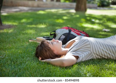 Young college student lying down on grass at campus lawn