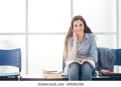Young college student reviewing before a test in the waiting room, she is reading a textbook and smiling