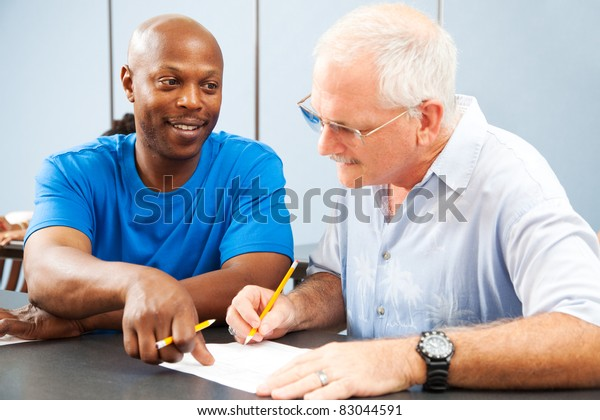 Young college student tutoring an older classmate.