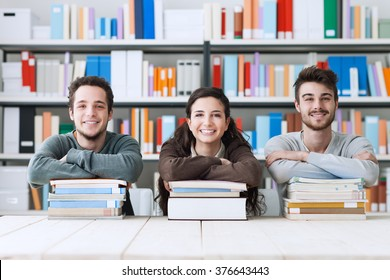 Young college students at the library studying together, they are smiling at camera and leaning on a pile of books