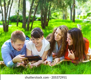 Young college students using tablet computer while doing homework in the park