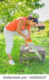 Young colombian emancipated woman sawing wood with handsaw in garden