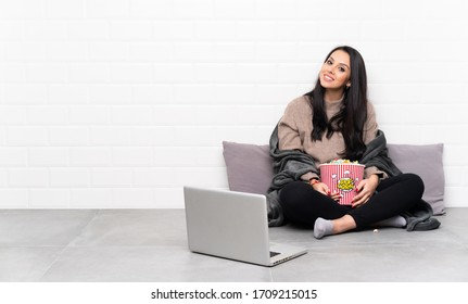 Young Colombian girl holding a bowl of popcorns and showing a film in a laptop with arms crossed and happy