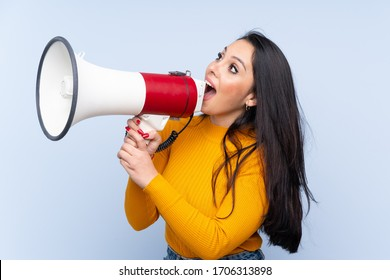 Young Colombian girl over isolated blue background shouting through a megaphone