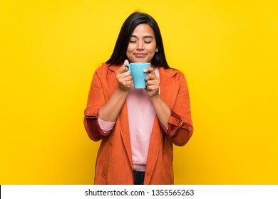 Young Colombian girl over yellow wall holding a hot cup of coffee