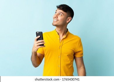 Young Colombian man using mobile phone isolated om blue background looking up while smiling
