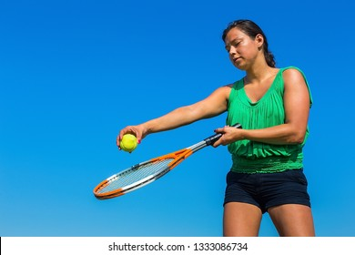 Young colombian woman holding tennis racket and ball against blue sky