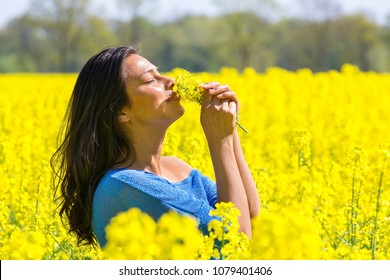Young colombian woman smelling flowers in yellow rapeseed field