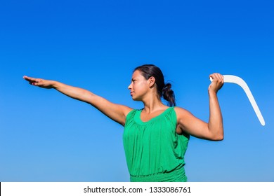 Young colombian woman throwing white boomerang in blue air