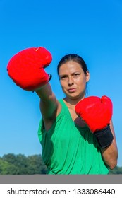 Young colombian woman wears red boxing gloves outdoors