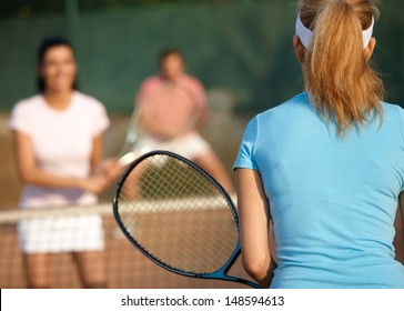 Young companionship playing mixed doubles on tennis court.