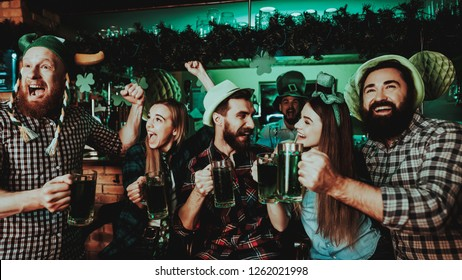 Young Company Are Celebrating St Patrick's Day. Bar Counter. Alcohol Handling. Black Beard. Smiling Teenagers. Good Festive Mood. Bright Lights. Club Visitors. Funny Hats. Glasses With Beer.