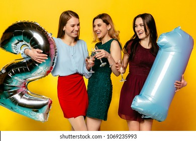 Young company of cheerful lovely girls in stylish dresses celebrating 21st anniversary, birthday party, holding helium balloons. Isolated over yellow background.