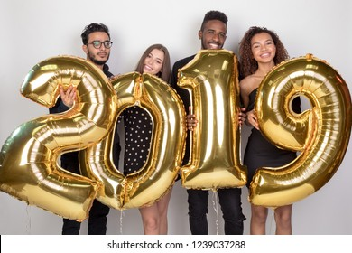 Young company of friends holding sign 2019 made of golden balloons for new year on white background.