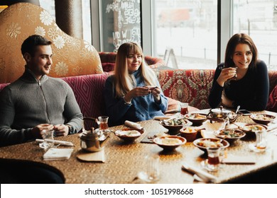 A young company of people is smoking a hookah and communicating in an oriental restaurant. Lebanon cuisine served in restaurant.  Traditional meze lunch