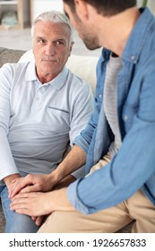 young compassionate man holding hand of unhappy elderly senior father