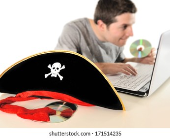 Young with Computer copying dvd and pirate hat representing illegal downloads and copyright violation isolated on white background