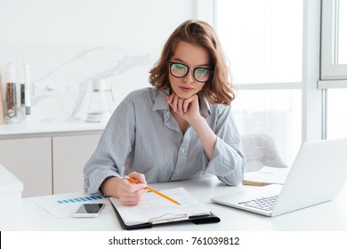 Young concentrated businesswoman in glasses and striped shirt working with papers at home