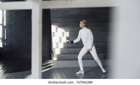 Young concentrated fencer woman practice fencing exercises and training for competition in studio indoors