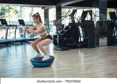 Young concentrated sportswoman standing on special rubber sphere and squatting in gym.