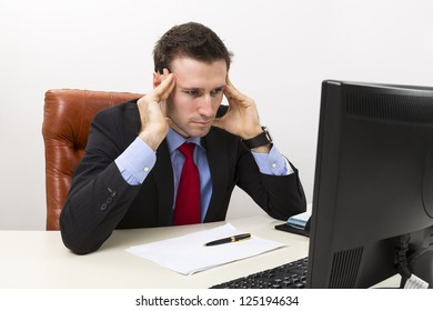 Young concerned businessman in the office looking at computer display and thinking about business problems.