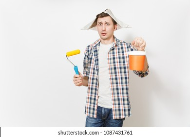 Young concerned man in newspaper hat holding paint roller for wall painting and empty paint bucket with copy space isolated on white background. Instruments for renovation room. Repair home concept