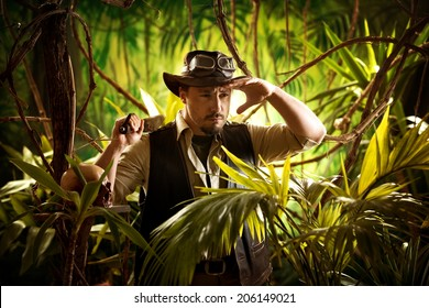 Young confident adventurer in the jungle holding a machete and looking around.
