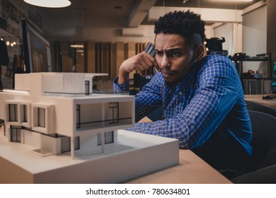 Young confident African American black male architect working on a private house project in the office, studying mansion model