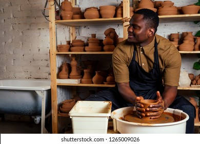 young and confident afro american man in a black apron sculpts a potter from a clay pottery workshop. clay pot in the hand of the latin artist
