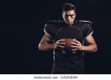young confident american football player with ball in hands looking at camera isolated on black