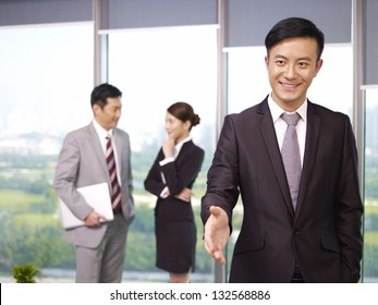 young confident asian business executive reaching out for a handshake.