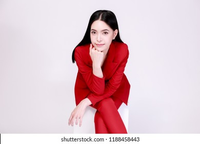 Young confident Asian woman in red elegant suit with pants posing sitting in half body isolated over white background