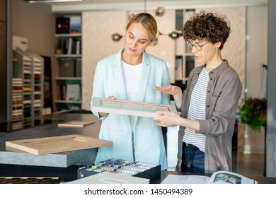 Young confident assistant of gift shop offering picture frame to client