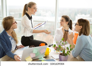 Young confident attractive businesswoman leading a business meeting or presentation with her creative team at the modern office explaining something smiling joyfully.