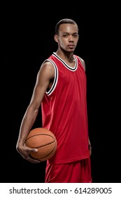 Young confident basketball player standing with ball and looking at camera isolated on black