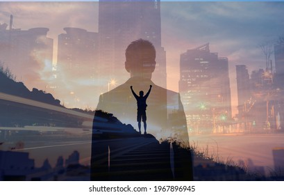 Young confident business man facing the city view. Man celebrating on a mountain top. People vision and inner strength, never giving up concept.