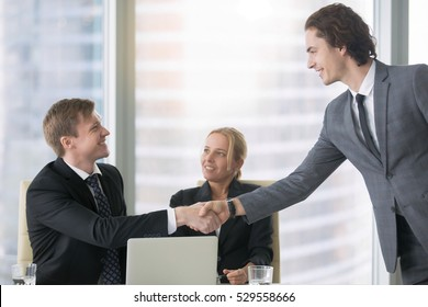 Young confident business man introducing himself at business meeting to his partners. Portrait of two smiling businesspeople in suits making agreement, greeting each other, shaking hands. Indoor