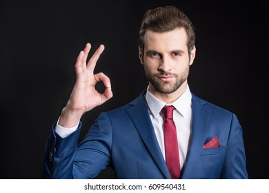 Young confident businessman showing ok gesture and looking at camera  isolated on black