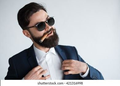 young confident businessman smoking a cigar and fixing his black suit with confidence on white background. Arrogant rich bearded man in sunglasses