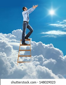 young confident businessman standing at the ladder high in the sky pulls hands to the sky / young man in shirt and tie pulls hands to the sky on top of the ladder on heaven
